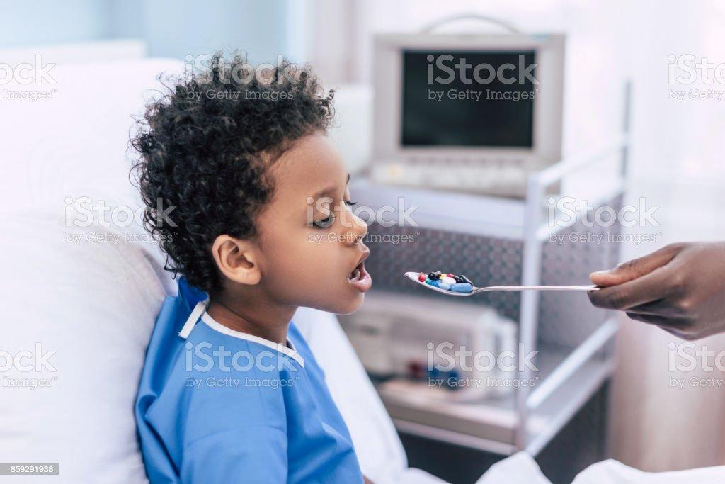 african american boy taking medicines stock photo