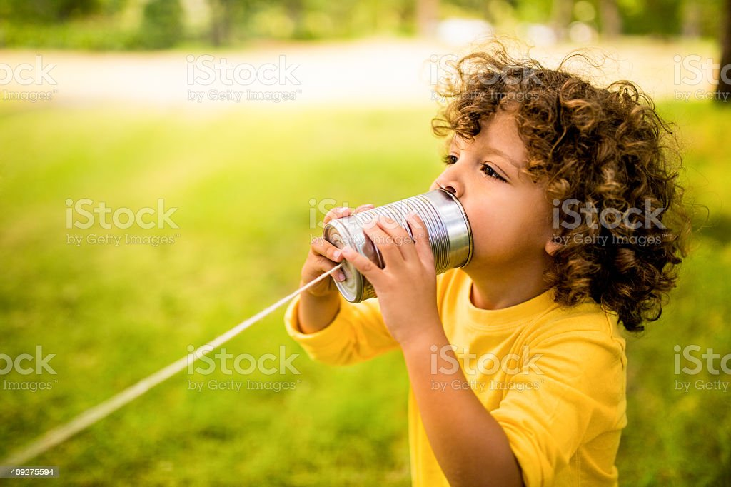 African American boy talking into tin can phone in park stock photo