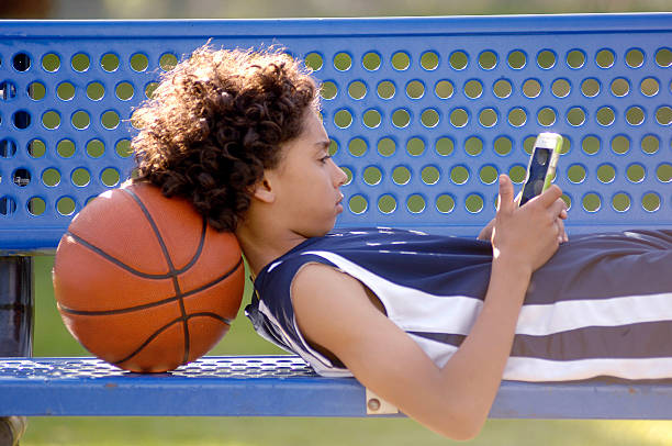 African American boy texting on a mobile phone. stock photo