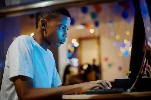 African american boy using a computer at night stock photo