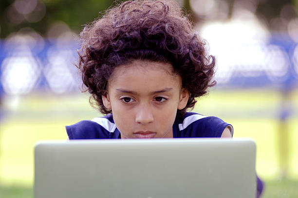 African American boy using a laptop computer outside stock photo