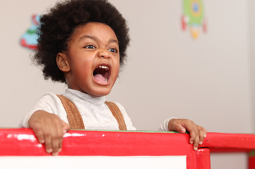 African American boy with curly hair shouting while playing at the playground, kid having fun on playground.