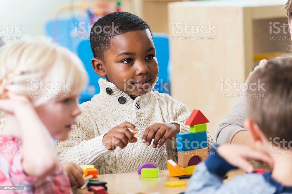 An African American boy in preschool or kindergarten, sitting with a...