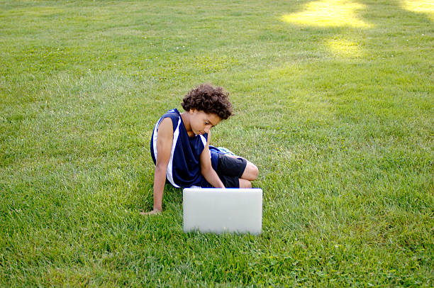 African American boy working on a laptop computer outside. stock photo
