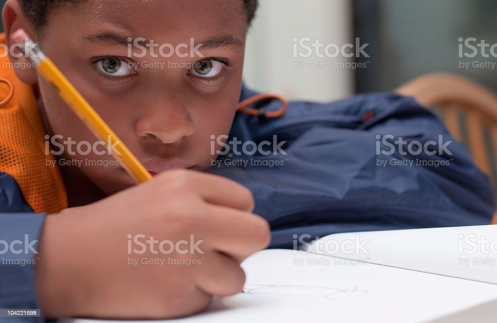 African American boy writing in notebook royalty-free stock photo