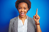 istock African american business executive woman over isolated blue background pointing finger up with successful idea. Exited and happy. Number one. 1162414755