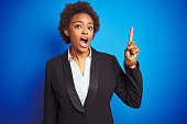 istock African american business executive woman over isolated blue background pointing finger up with successful idea. Exited and happy. Number one. 1212247012