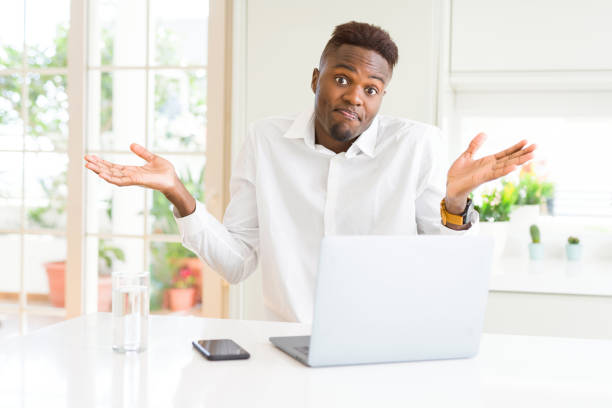 African american business man working using laptop clueless and confused expression with arms and hands raised. Doubt concept. African american business man working using laptop clueless and confused expression with arms and hands raised. Doubt concept. shrugging stock pictures, royalty-free photos & images