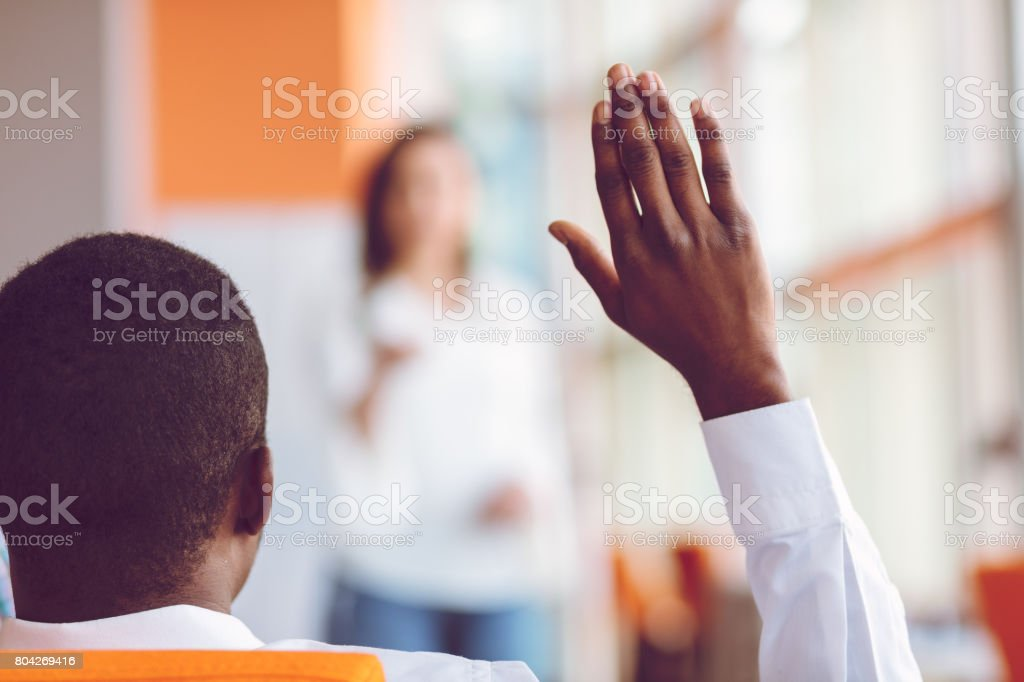 African american Business people Raising there Hand Up at a Conference to answer a question stock photo