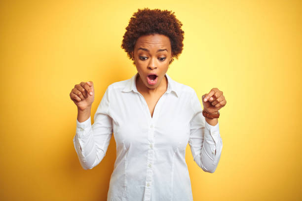 african american business woman over isolated yellow background pointing down with fingers showing advertisement, surprised face and open mouth - smile woman open mouth foto e immagini stock