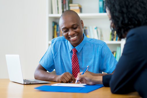 istock African american businessman and businesswoman signing contract 1210046588