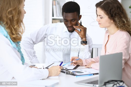 istock African american businessman at meeting in office, colored in white. Negotiation or hard decision concept 687461044