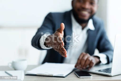 Partnership concept. Smiling young African American businessman extending hand to shake.