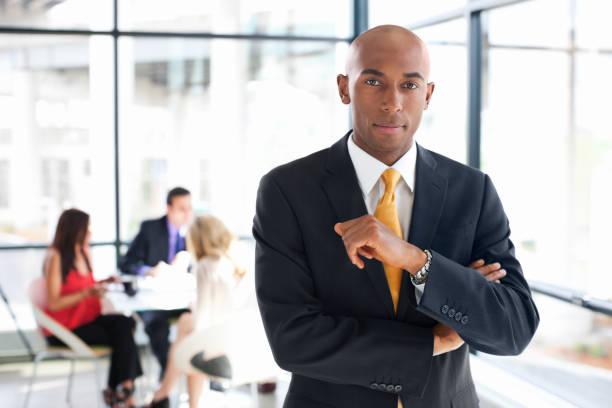 African American Businessman in Glass Office with Team, Copy Space stock photo