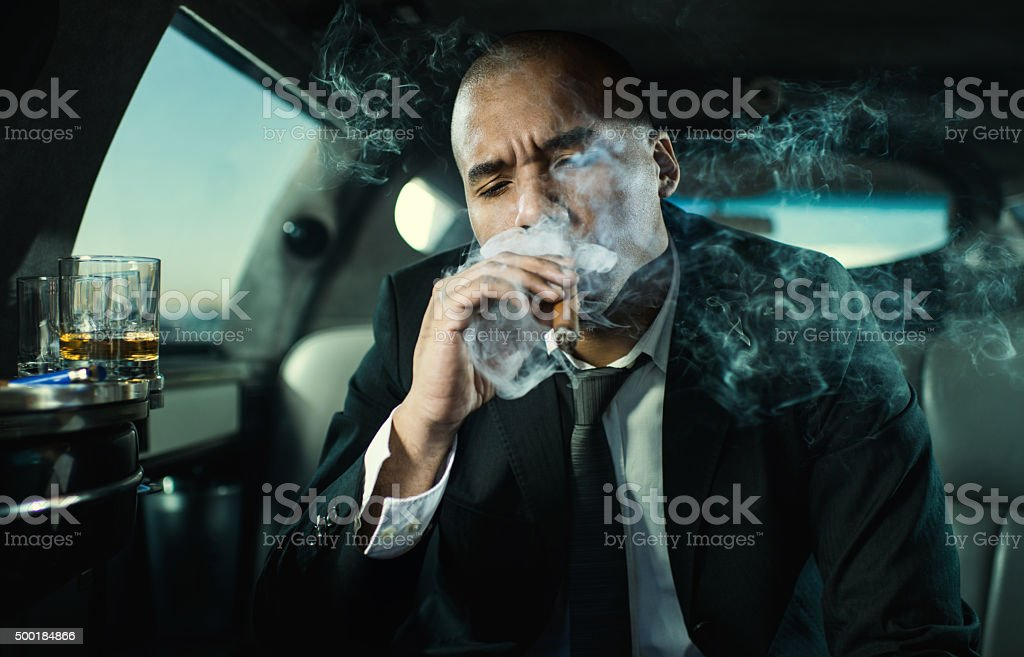 African American businessman in limousine smoking a cigar. stock photo