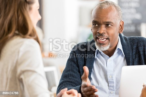 Handsome senior African American businessman talks with a client or colleague over a cup of coffee.