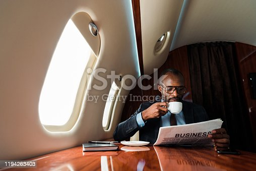 African american businessman reading business newspaper while drinking coffee in private plane