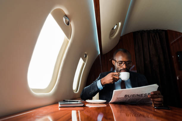 African american businessman reading business newspaper while drinking coffee in private plane stock photo