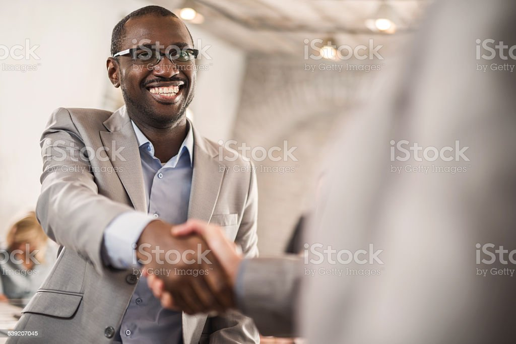 African American businessman shaking hands with his colleague. stock photo