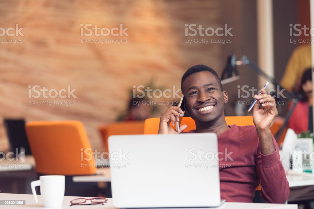 African American businessman sitting at the computer in startup office stock photo
