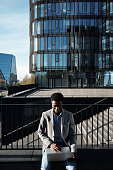 African American businessman sitting outdoors, working on laptop and smiling  against background of modern office buildings and staircase