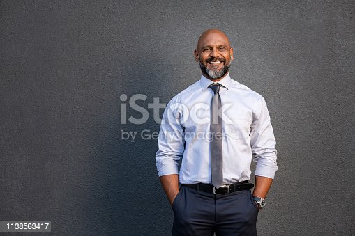 Portrait of successful black businessman standing against grey wall. Handsome senior entrepreneur wearing blue tie and formal clothing smiling and looking at camera. Mature happy man with hands in pocket isolated on grey background with copy space.