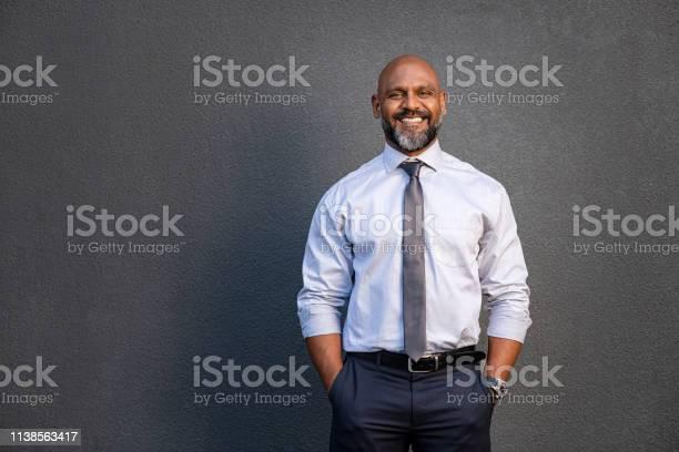 African american businessman smiling on grey picture id1138563417?b=1&k=6&m=1138563417&s=612x612&h=de2qdm8zrxrx7 32kk7owoe fuxobqu3dwnz4hx dzm=