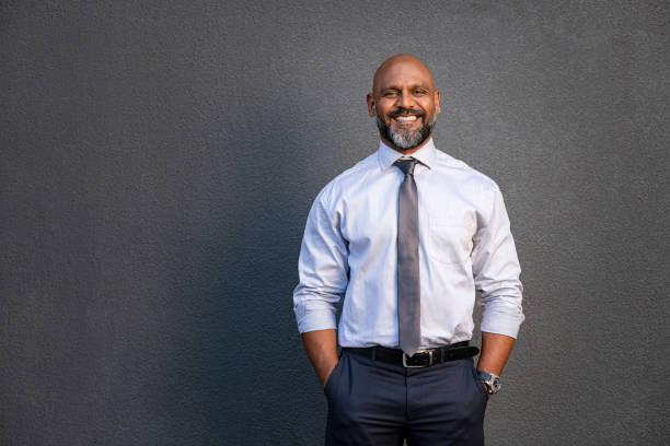 homme d'affaires afro-américain souriant sur le gris - homme photos et images de collection