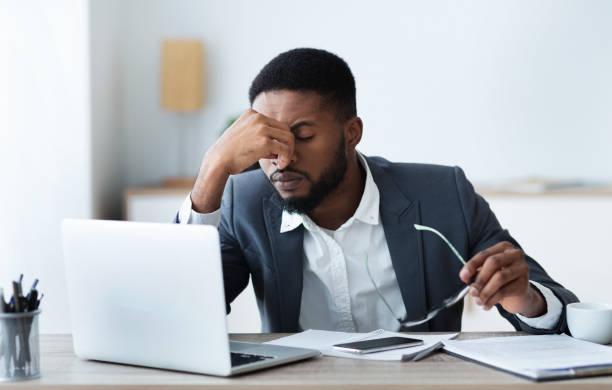 afroamerikanischer geschäftsmann müde von langer zeit arbeit auf laptop - frustration stock-fotos und bilder