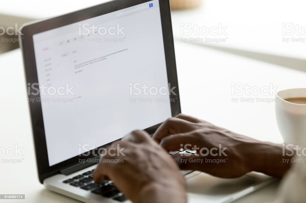 African american businessman typing e-mail on laptop using online application stock photo
