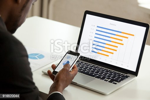 istock African american businessman using devices for business, over shoulder view 916520044