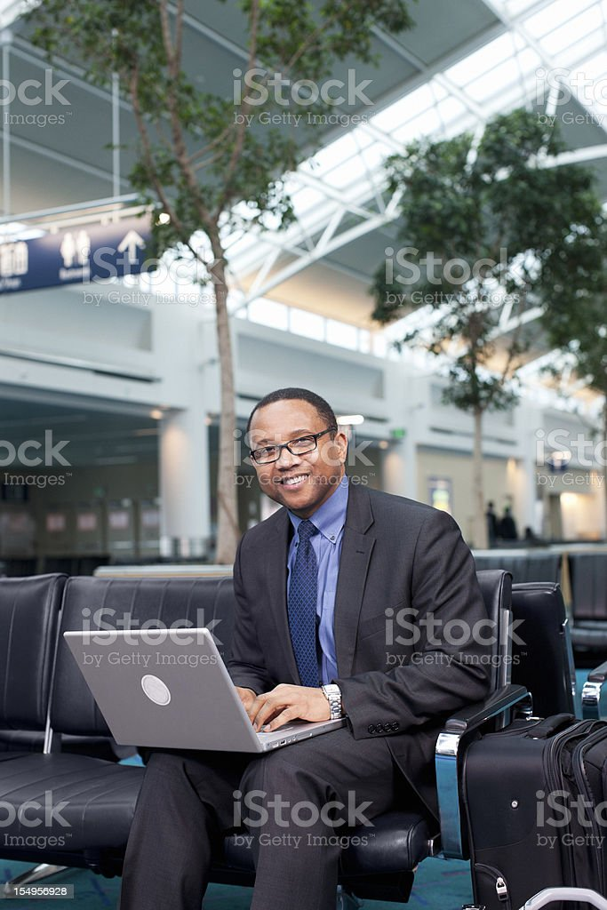 African American Businessman Using Laptop in Airport Lounge, Copy Space royalty-free stock photo