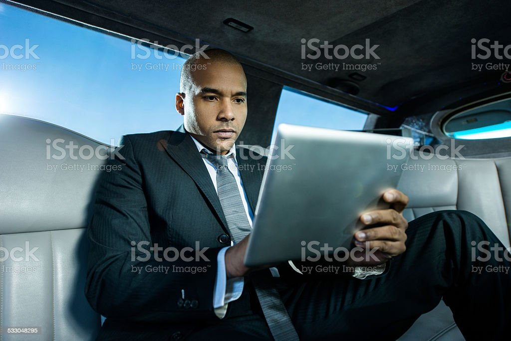 African American businessman using touchpad in a limousine. stock photo