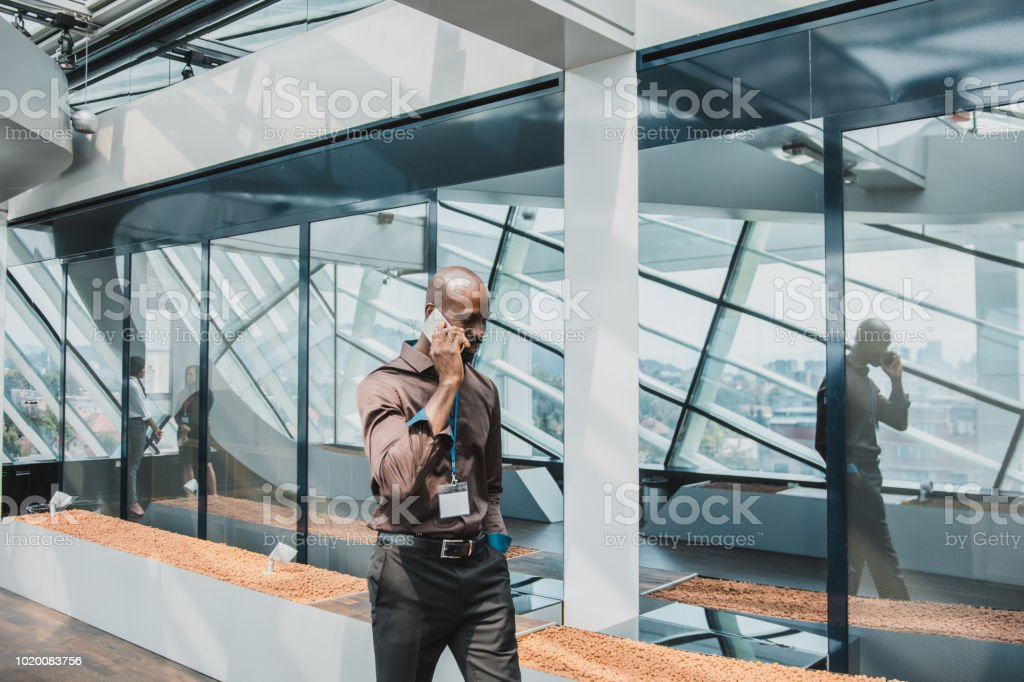 African American businessman walking and using smart phone in the...