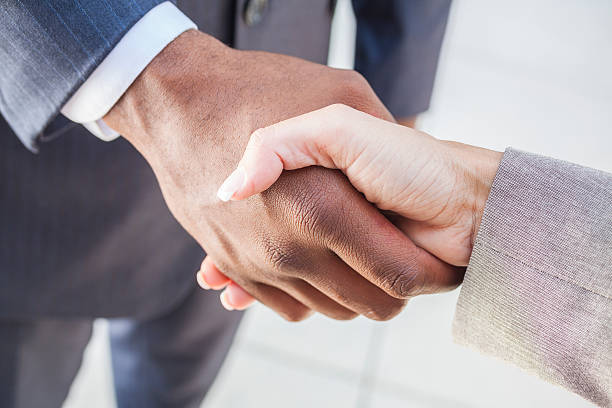 African American Businessman & Woman Shaking Hands stock photo