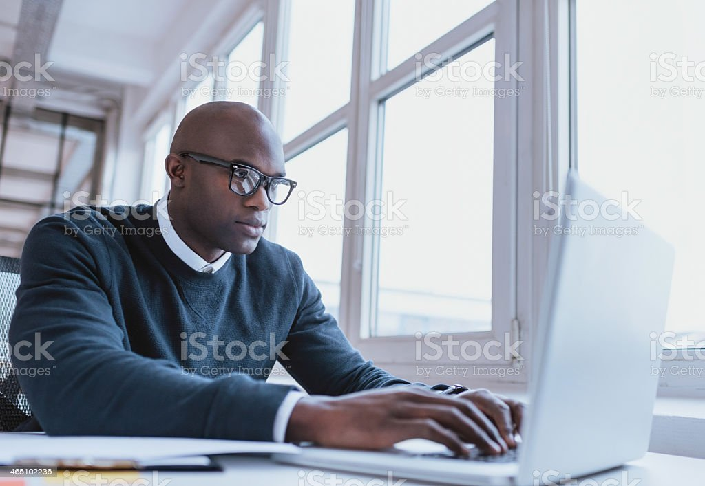 Image of african american businessman working on his laptop. Handsome...
