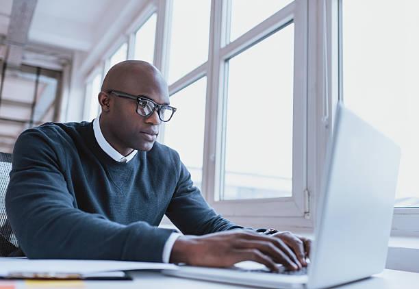 afrikanische amerikanische geschäftsmann arbeiten auf seinem laptop - mann sucht mann stock-fotos und bilder