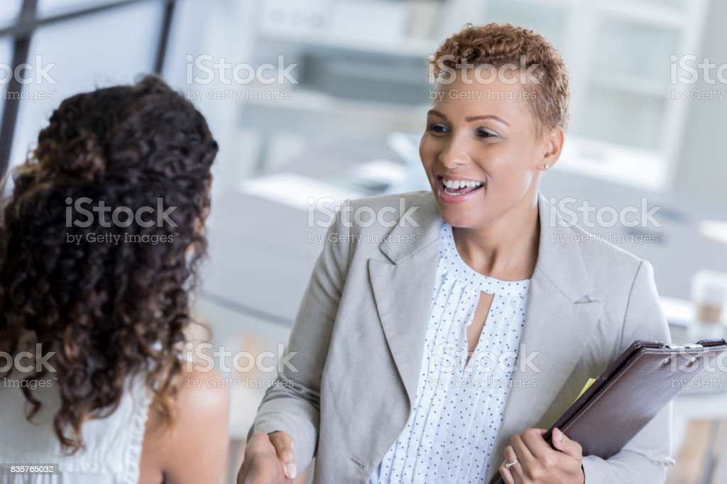 African American businesswoman greets client stock photo