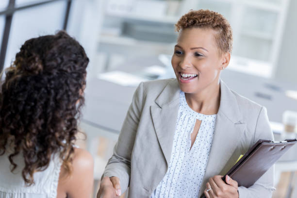 African American businesswoman greets client - foto stock