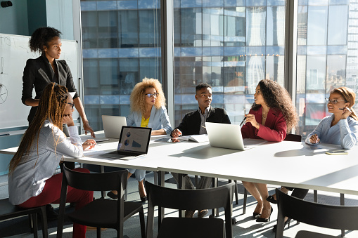 Young African American businesswoman lead meeting with multiethnic colleagues, communicate interact in office. Female ethnic coach or boss present at workplace, brainstorm with diverse businesspeople.