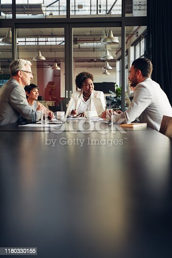 African American businesswoman sitting with her diverse team around a table in an office boardroom discussing work