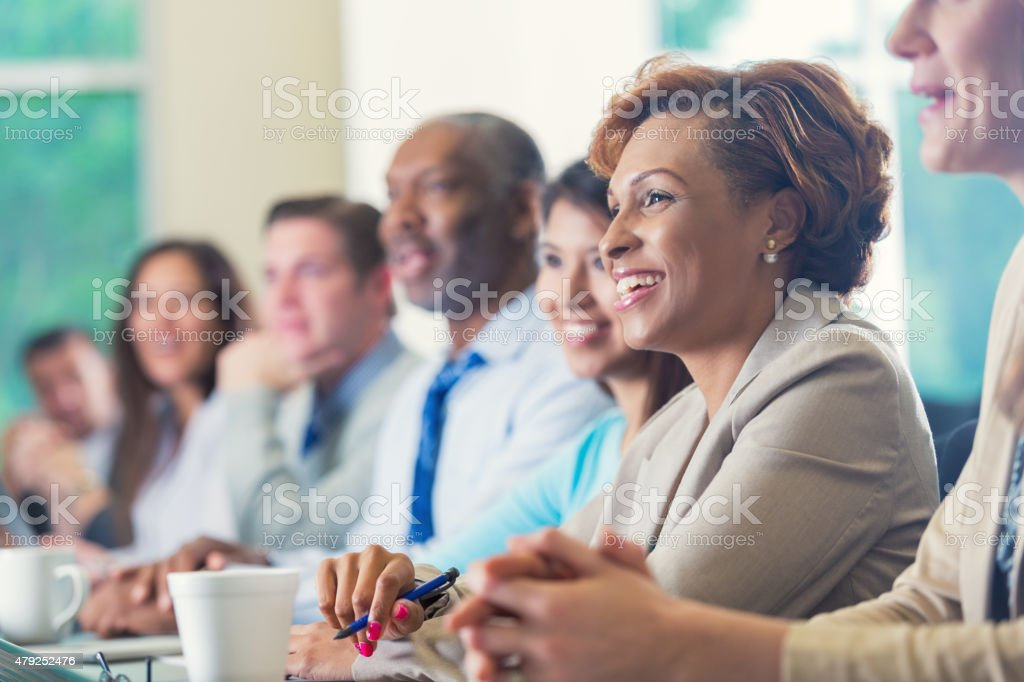 African American businesswoman listening to seminar speaker at business conference stock photo