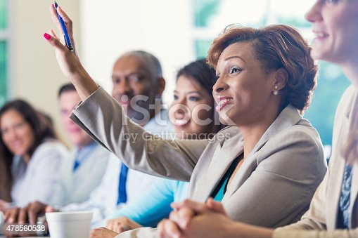 istock African American businesswoman raising hand, asking question in business conference 478560538
