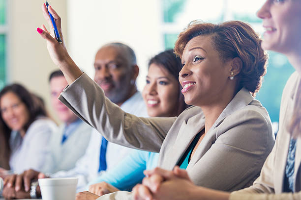 afro-americana donna d'affari alzando le mani, ponendo domande in conferenza di lavoro - formazione degli adulti foto e immagini stock