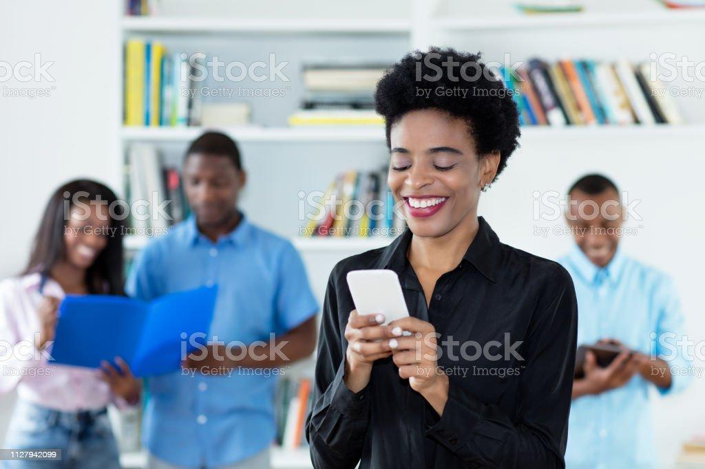 Empresaria afroamericana está enviando el mensaje con el teléfono - foto de stock