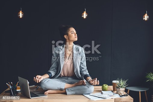 istock african american businesswoman sitting in lotus pose on table while meditating in office 823349870