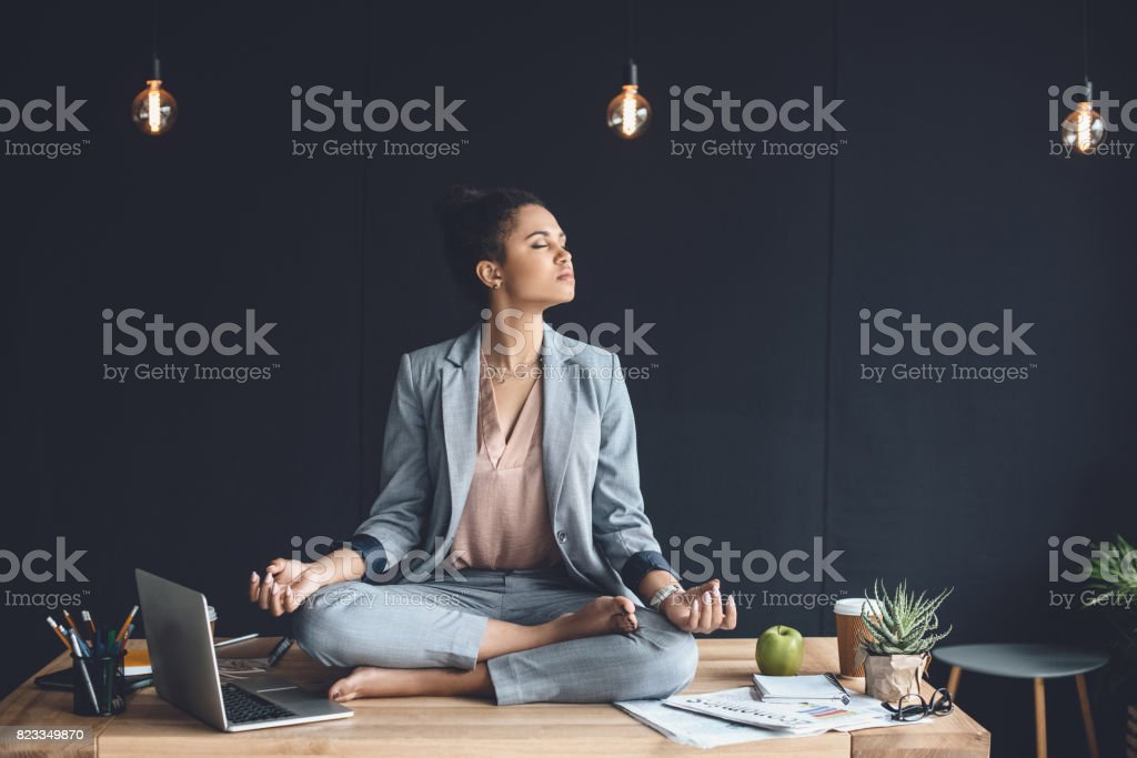 african american businesswoman sitting in lotus pose on table while meditating in office stock photo