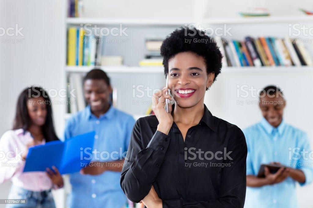 African american empresaria hablando en el teléfono con sus colegas - foto de stock