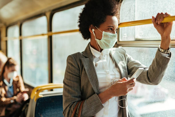 African American businesswoman with face mask texting on the phone while traveling by bus. Black businesswoman with protective face mask using smart phone and looking through the window while commuting by bus. bus stock pictures, royalty-free photos & images