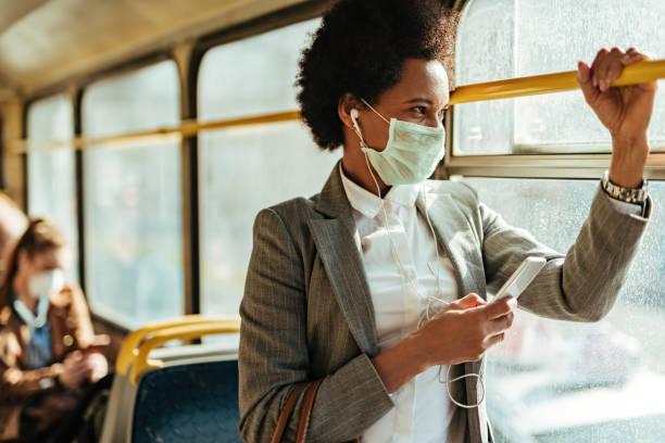afrikaanse amerikaanse onderneemster met gezichtsmasker dat op de telefoon texting terwijl het reizen door bus. - forens stockfoto's en -beelden